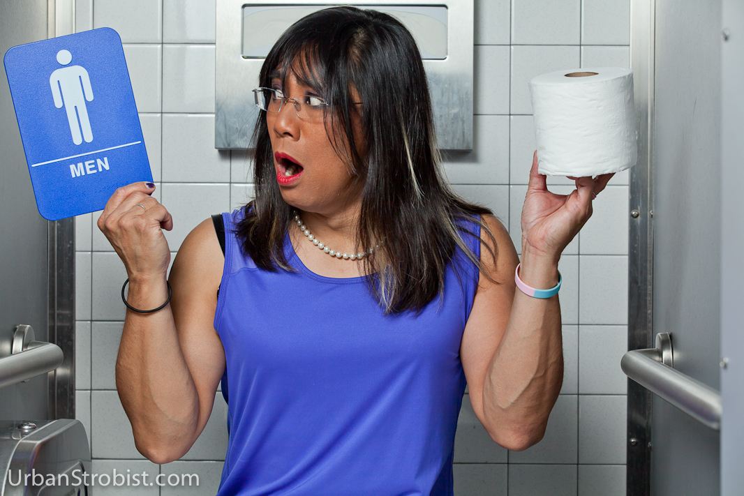 Transgender female in restroom stall with bathroom sign
