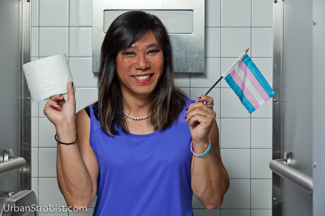 Transgender female in restroom stall with toilet paper and Transgender Pride Flag